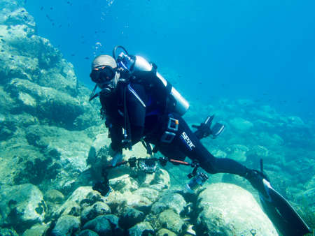 buoyancy: Avlaki,Greece - June 15 2016 : A male scuba diver with a camera shows good buoyancy during a dive