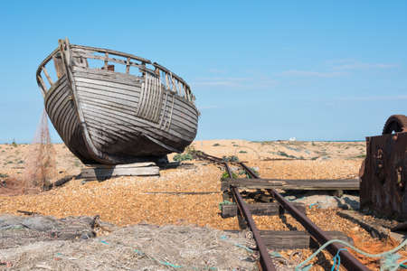 Old wooden fishing boat falling to pieces on a beach Stock Photo