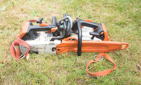 Two small chainsaws clipped together ready to start work