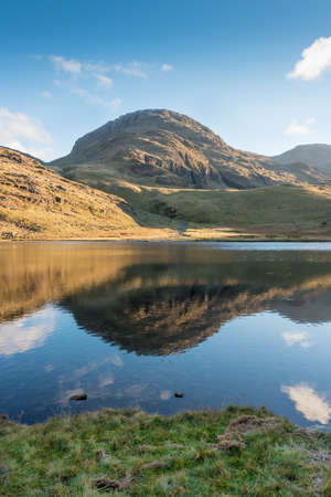A Fell in the Lake District is reflected in Styhead Tarn close to Scarfell Pike.