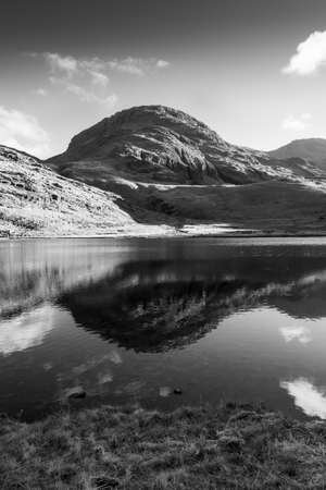 Black and White image of a  Fell in the Lake District is reflected in Styhead Tarn close to Scarfell Pike. Standard-Bild