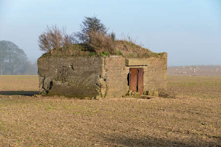 Derelict World War 2 pillbox in a field near Dover,UK. Bushes are growing on the roof.