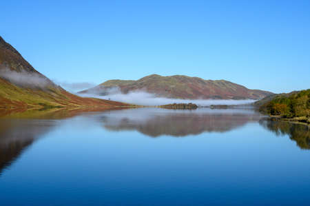 View across Crummock Water in the Lake District looking towards Low Fell. A bank of mist lies at the top of the lake