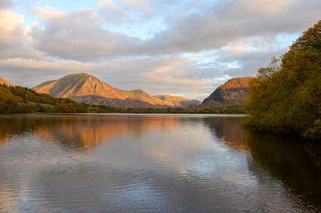 Sunset reaches the top of Grasmoor Fell looking across Loweswater in The Lake District,Cumbria,UK.