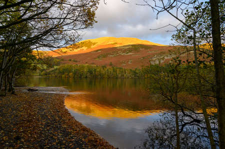 Looking across Loweswater the sun sets on the top of Askhill Knott in The Lake District,Cumbria,UK. Reklamní fotografie