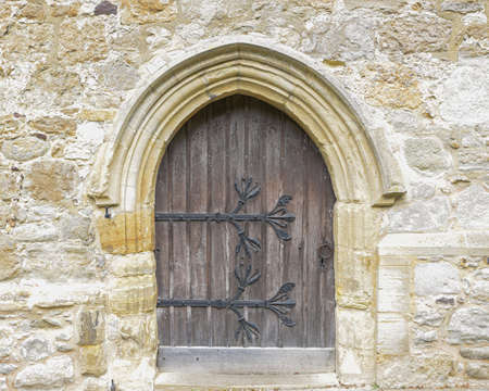 Old wooden door with large iron hinges in a wall of a church