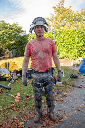 Arborist or Tree Surgeon wearing safety equipment covered in sawdust. Stok Fotoğraf