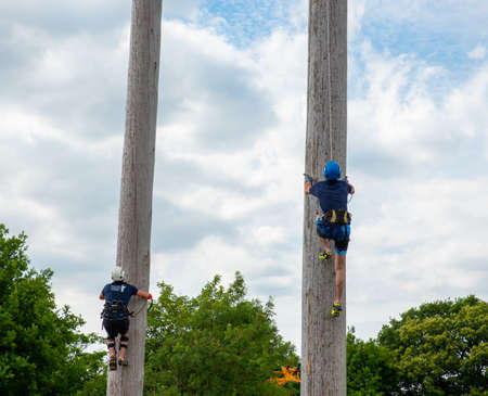 Kent County Show , UK - JULY 07 2017 :Competitors climb a 25m tall pole to see who is the fastest in a pole climbing competition