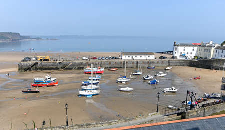 Tenby, Wales - April 15 2019 : The boats in Tenby Harbour at low tide Sajtókép