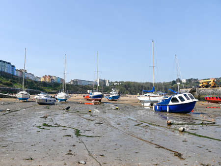 Tenby, Wales - April 15 2019 : The boats in the harbour at Tenby at low tide showing the mooring chains