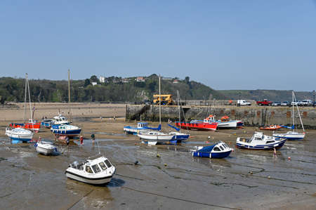 Tenby, Wales - April 15 2019 : The boats in Tenby Harbour at low tide showing the mooring lines.