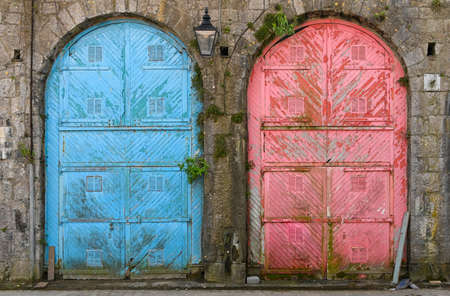 Pair of large  colourful old doors with peeling paint set in a stone building.