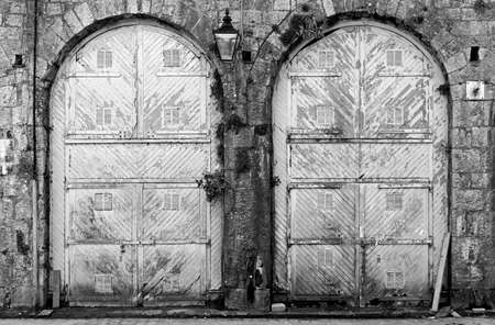 Black and White image of two large old doors .