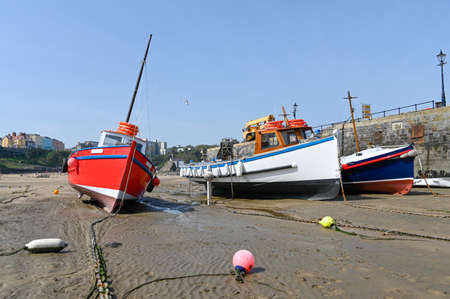 Boats on the sand in Tenby harbour at low tide.