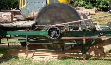 Old fashioned belt driven circular saw ready to cut a log.