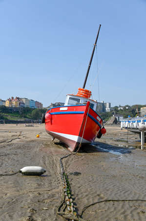 Red boat on the beach in Tenby harbour at low tide