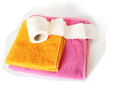 The roll to a toilet paper lies on a pile of towels Stock Photo