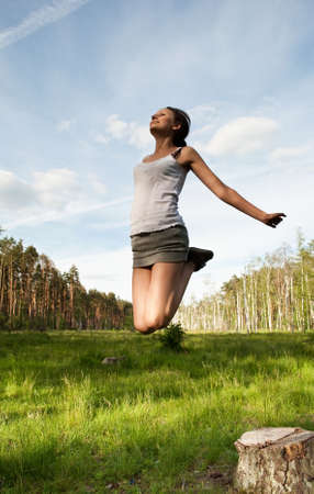 The young girl has jumped against wood and the sky Stock Photo