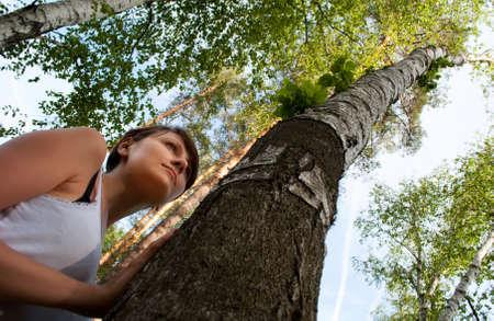 MÅ'oda dziewczyna leans przeciwko Brzoza przeciwko niebo i drewna Zdjęcie Seryjne