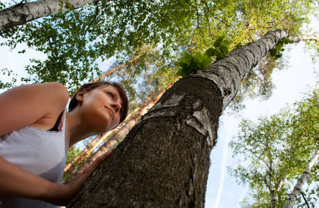 The young girl leans against a birch against the sky and wood