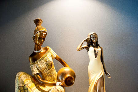 Two figurines of the woman, one African with a jug, other white. photo