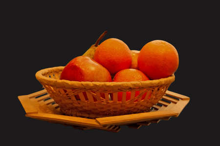The isolated basket with oranges, an apple and a pear on a dark blue background