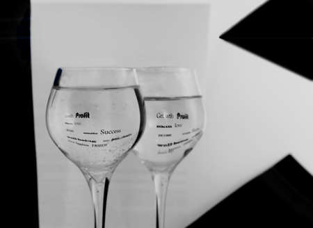 Two black-and-white glasses in water are reflected words. Stock Photo