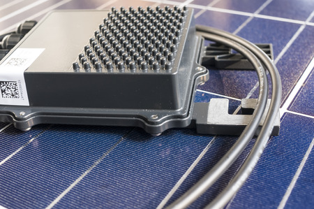 optimizer: solaredge, solar panel power optimizer close up, solar cells background Editorial
