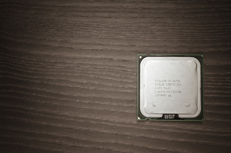 intel: Intel Core 2 Duo cpu front, close up on a wooden background Editorial