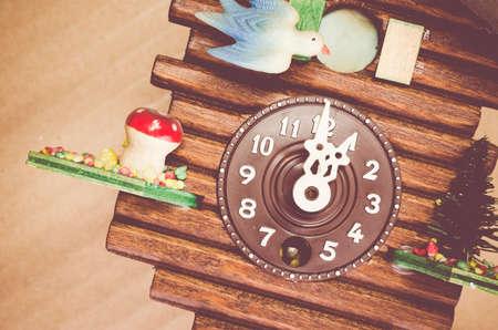 wooden clock: cuckoo wall clock dial close up, one oclock