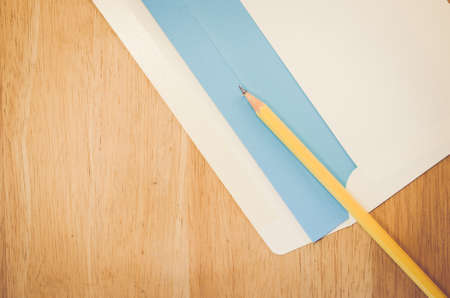 dopisní papír: white envelope pencil and blue writing paper on a natural wood surface
