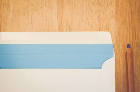 wood surface: white envelope pencil and blue writing paper on a natural wood surface