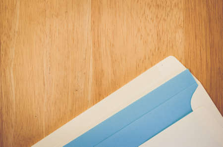 writing on paper: white envelope and blue writing paper on a natural wood surface