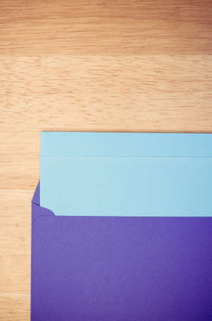 writing on paper: dark blue envelope and blue writing paper on a natural wood surface