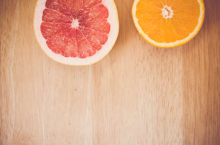 half  cut: half cut orange and grapefruit - autumnal fruits still life on a wood background Stock Photo