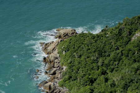 Florianopolis coast aerial view from paraglide. Aerial top view of beautiful tropical island and sea waves crashing coastline cliff during sunny summer day.
