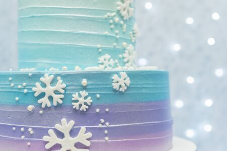 Two tier cake on blue background with unfocused lights