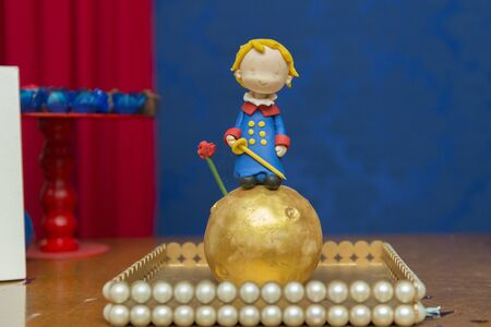 Kids birthday party decoration. Little prince theme party. Closeup of Little Prince in your small planet on blue background. Selective focus.