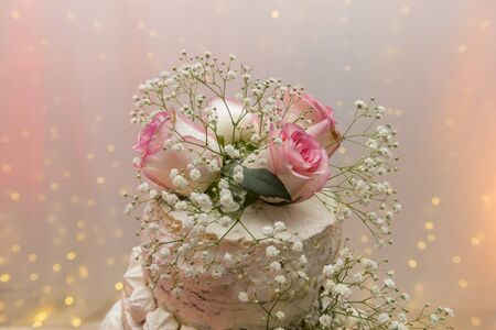 Close up of beautiful white tree tier cake with fresh flowers with fairly light and lanterns glowing in the background on a wooden rustic table. Selective focus. Copy space.