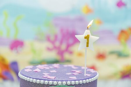 Lighted birthday candle in star shape with blurred background. 1 year anniversary, deep sea theme. Celebration, party and joy concept.