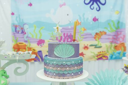 Cake table overview decorated with the seabed theme. Children's party with octopus, seahorse, oysters, corals and colorful balloons. Party and fun concept. Stock Photo