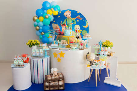 Sweet table and big cake for first birthday. Candy bar with a lot of candies, cupcakes and sweet cakes. Little prince theme party. Close up of decor party.