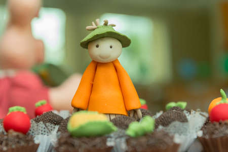 Tray with assorted candies of different flavors. Personalized and decorated sweets for the farm or rural theme. Handmade candies in the shape of scarecrow, corn, tomatoes and carrots. Selective focus.