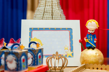 Kids birthday party decoration. Blue fake cake with candle. Little prince theme party. Decorated table for child birthday celebration. Close up of decor party.