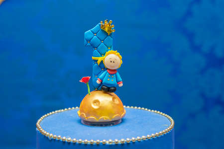 Number one candle on a blue background. Little prince theme. Fake birthday cake with personalized candle for first birthday for boy. Imagens