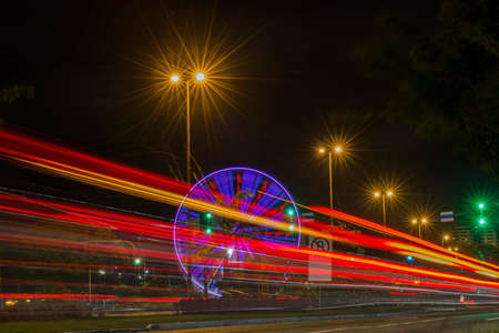 Long exposure of colorful ferris wheel and light trails on the expressway road at night. Time exposure of traffic lights on avenue in Florianopolis. Concept of movement and nightlife. Imagens