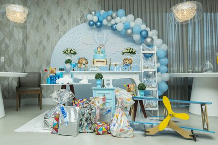 Boy's birthday party with bluish pastel colors decoration. Decor with aviator theme with teddy bear, clouds, candy. Delicate candy table with beautiful decorated cake.