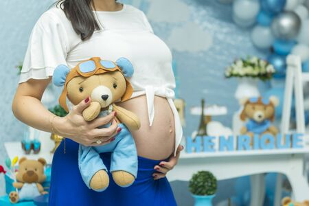 Close-up of torso of young pregnant model standing in baby shower and holding a teddy bear side her belly. Future mom expecting child. Maternity concept. Copy space for text message.