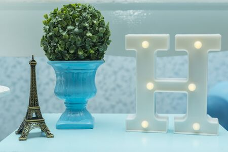 Decoration with miniature Eiffel tower, blue ceramic vase and the letter H.