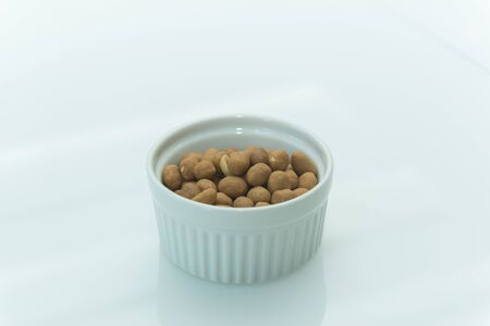 Roasted salty peanuts on white background with copy space. Japanese peanuts in a white ceramic bowl on a white table. Selective focus.